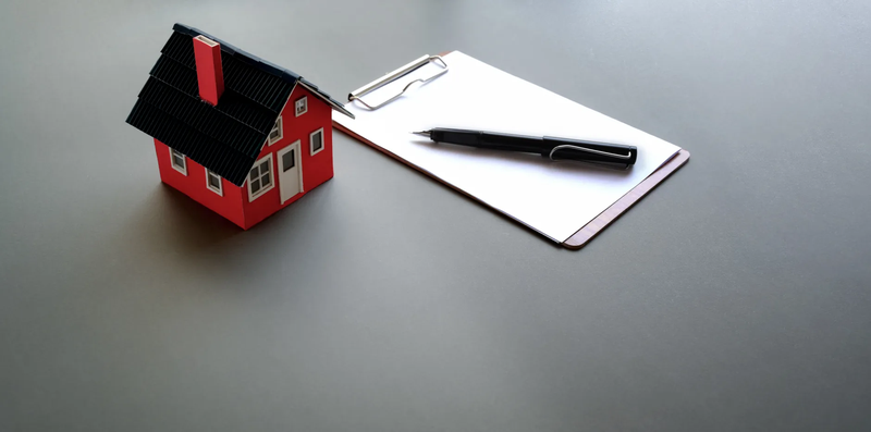 small house model and clipboard with paper and pen
